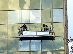Two workers on a suspended scaffold on a building.