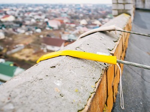 View of ropes supporting a suspended scaffold that are protected from fraying.