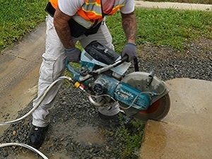 Construction worker using a handheld power saw to cut into a slab on the ground.