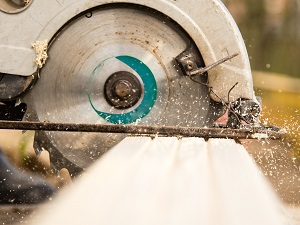 Close-up view of a circular saw cutting a piece of wood.