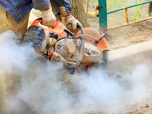 Worker using a handheld power saw that is producing sparks and a lot of visible dust.