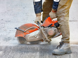 Worker using a handheld power saw to cut into the concrete road.