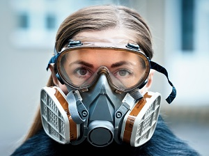 A worker wearing a respirator and safety goggles.