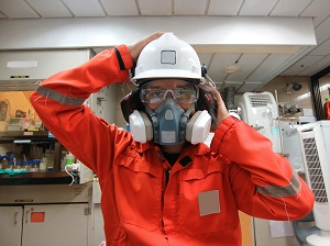 Worker wearing a respirator, safety glasses, ear muffs and a hard hat.