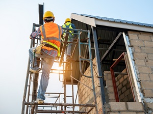 Worker climbing onto a supported scaffold from the side.