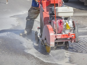 Construction worker wearing rubber boots operating a walk-behind saw to cut into the road.