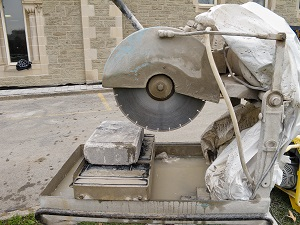 Stationary masonry saw sitting at a construction site, not currently in use.