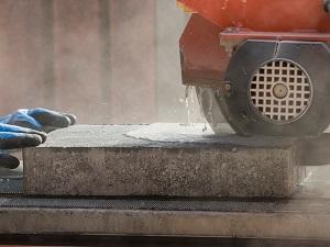 A masonry saw cutting concrete pavers using the wet method.