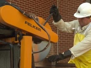 A worker wearing PPE operating a stationary masonry saw to cut pavers.