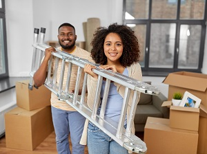 A man and a woman carrying a ladder together inside a home.