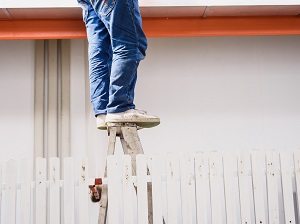 A person dangerously standing on the very top step of a step ladder.