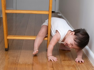 A crying baby stuck on the bottom rung of a ladder set up inside a house.