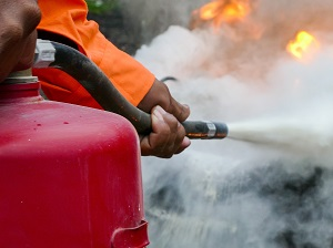 A worker using a fire extinguisher to put out a fire.