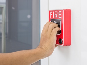 A worker pulling the fire alarm in the hallway of a building.