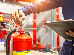 An inspector with a clipboard inspecting a fire extinguisher.