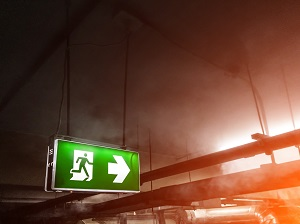 An exit sign pointing the way in a building where there is a fire.