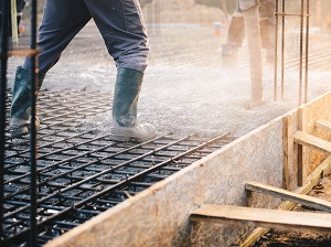 Worker standing on rebar pouring cement into formwork.