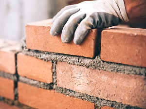 Worker wearing gloves building a brick wall with mortar.