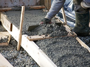 Worker wearing gloves spreading out wet concrete during construction.