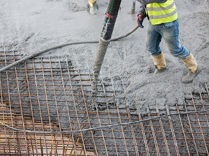 Worker wearing boots and gloves pouring concrete onto rebar formwork.
