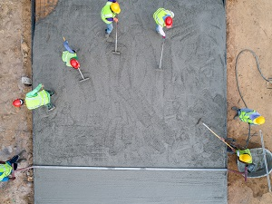 Overhead view of several workers spreading out wet concrete.
