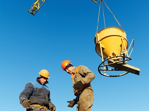 Two workers underneath a concrete bucket.