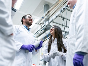 Laboratory workers in lab coats talking to each other and smiling.