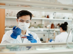 Lab worker wearing gloves, face mask and safety glasses.