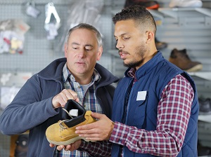 Two men shopping for work boots in a store.