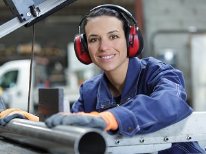Industrial worker wearing earmuffs for hearing protection.