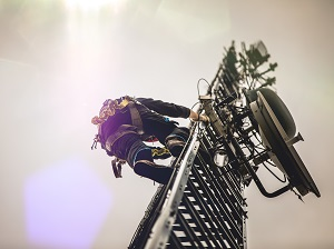 Worker wearing fall protection climbing up a tower.