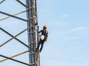 Worker wearing a hardhat and fall protection climbing up a tower.