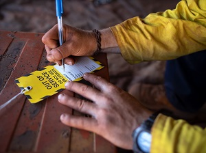 A worker filling out an out of service tag to place on electrical equipment that is defective.