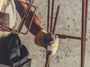 Construction worker holding rebar while wearing gloves and a tool belt.