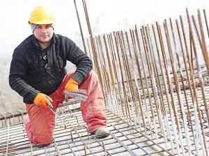 Construction worker kneeling down while tying rebar next to vertical rebar that is an impalement hazard.