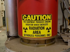 """Industrial equipment with a large yellow caution sign that says, """"Caution, This equipment produces ionizing radiation when energized, Radiation Area, Authorized Personnel Only."""""""