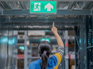 A worker pointing to the exit sign in a building.