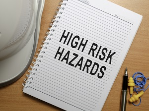 Hardhat and earplugs on a desk next to a notepad that says High Risk Hazards.