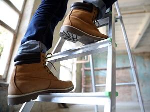 Worker climbing up a step ladder.
