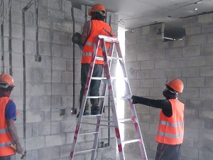 A worker standing backwards on a step ladder.