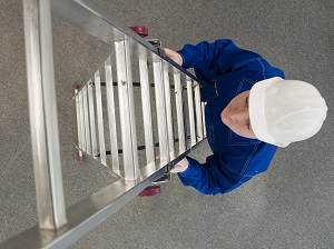 A vew from above of a worker wearing a hard hat climbing a step ladder.