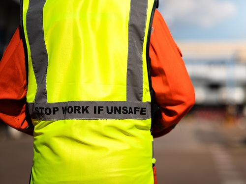 """Worker on a job site wearing a safety vest that says, """"Stop Work If Unsafe"""" on the back of the safety vest."""