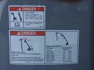 Warning stickers found on Aerial Lifts that warn against using near overhead power lines.