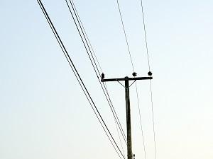 Overhead power lines against a blue sky.