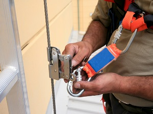 A person connecting a hook or carabiner to a vertical lifeline.