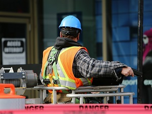 A worker wearing a hard hat, a safety vest and a personal fall arrest system in an aerial lift.