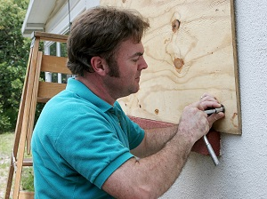A man putting plywood on the outside of a house over the windows.