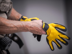 Worker putting on yellow and black work gloves.