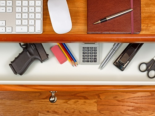 A desk drawer that has office supplies and a visible handgun.