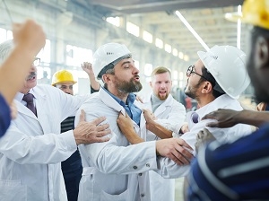 Two angry workers that look like they are fighting with each other while other workers surround them.